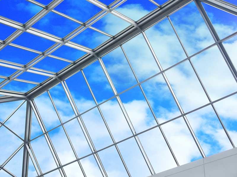 Blick auf den blauen Himmel durch eine Schrägverglasung